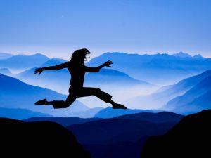 kvinna på språng mellan bergstoppar